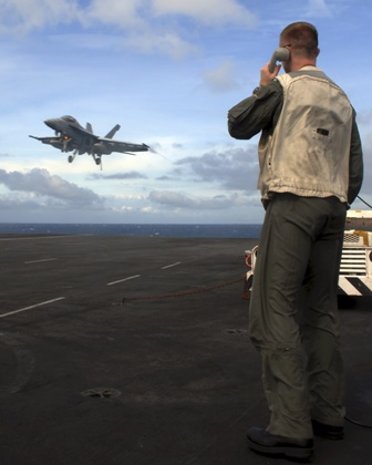 Seaman standing on the deck of an aircraft carrier talking on the phone