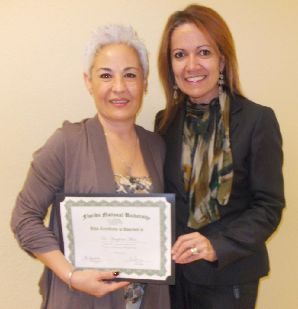 Ms. Carol Romero presents Dr. Mora with a certificate of appreciation