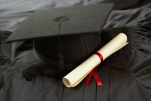 A graduation cap and gown with a diploma laying on top.