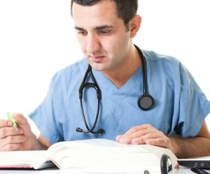 Male student nurse studying book