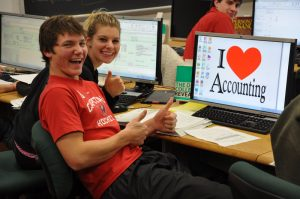 "Young college students working on a computer that says ""I love accounting"""