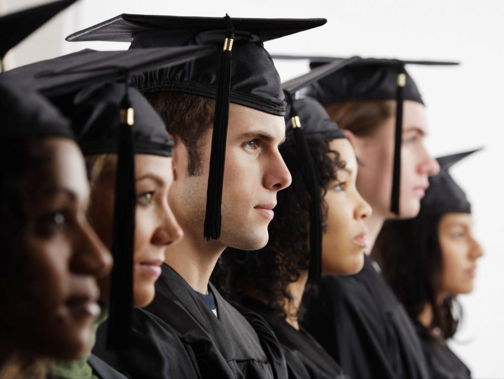 Group of college students wearing caps and gowns