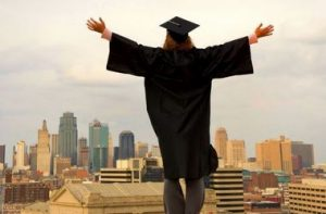Student in graduation cap and gown jumping with arms outstretched off a building rooftop