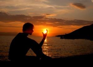 man sitting on beach in sunset