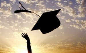 throwing graduation cap into sunset