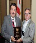 Men holding award plaque