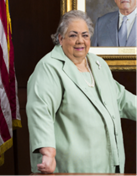 Woman posing next to portrait