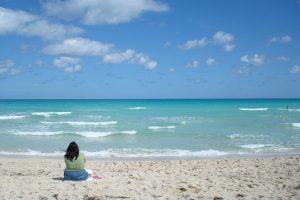 Woman sitting on beach looking at ocean