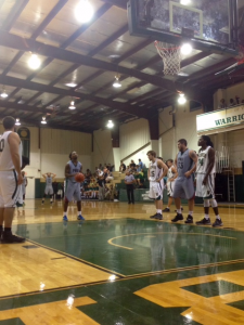 Basketball player in a gym taking a free throw while other players watch