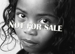 "Child with ""not for sale"" text on top of her"