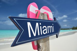 Sign pointing to Miami Beach with sandals on it
