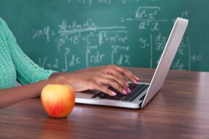 Student typing on lap top in classroom next to an apple