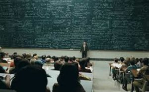 Huge chalkboard with professor teaching class in front of it