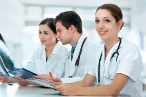 Two nurses and doctor looking at x-ray results