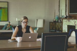 Young woman with glasses works on her laptop