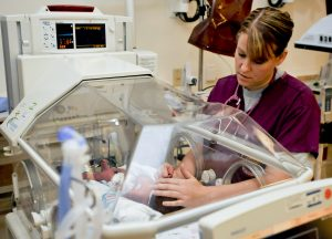 Nurse examines new born baby