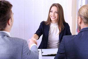 Women in business attire shaking a mans hand