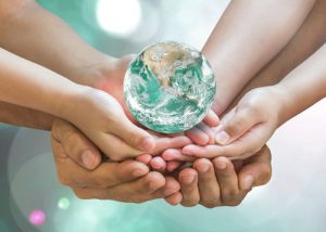 Hands of kids and adults holding a globe
