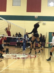 FNU Volleyball player in the air spiking ball over net