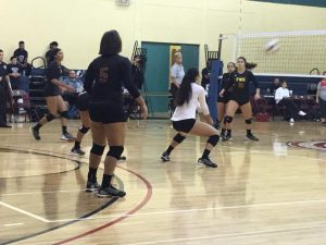FNU volleyball player crouches down to hit ball. Other players watch.