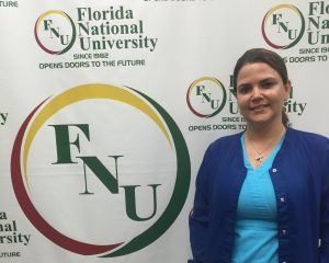 Woman in blue scrubs poses next to FNU logo