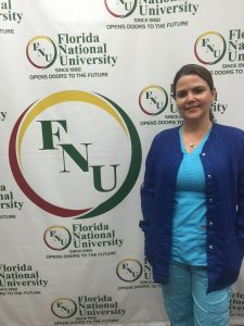 Woman wearing blue scrubs poses next to FNU logo