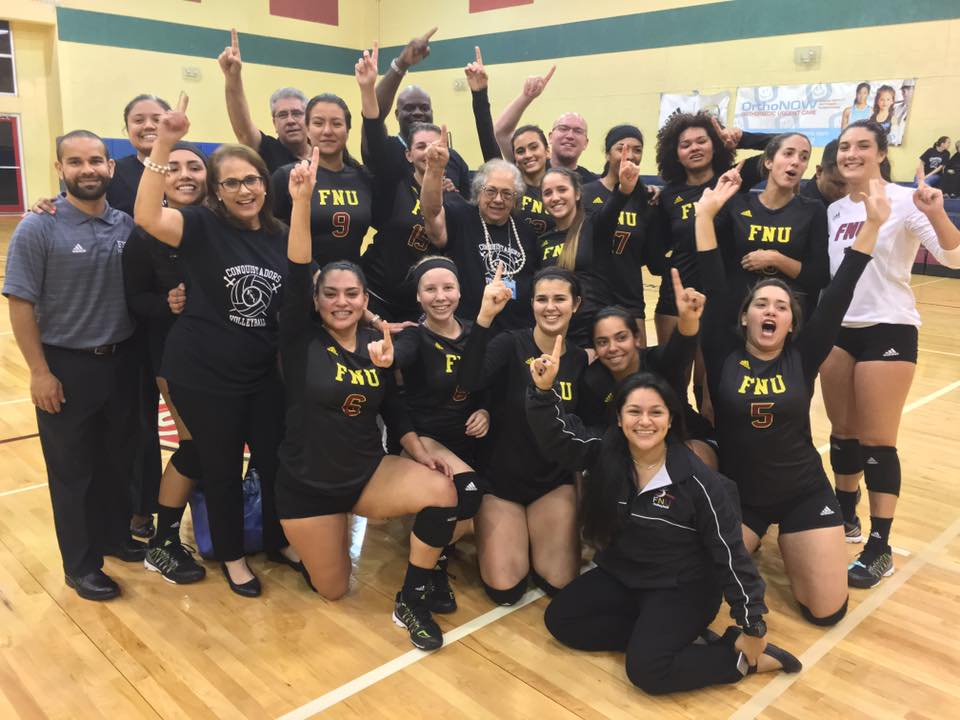 Volleyball players and FNU staff members hold up #1 with hand, celebrating their win