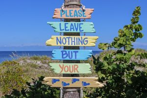 A sign made of driftwood on a beach that reads: please leave nothing but your footprints
