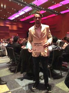Soccer player Rodrigo Costa holds up certificate at awards ceremony