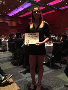Volleyball player Bianca Baez holds up certificate at awards ceremony