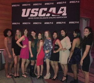 Lady Conquistadors Volleyball team pose for a picture in front of USCAA sign