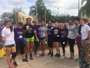 FNU Lady Conquistadors volleyball team huddles together for a picture outside a playground