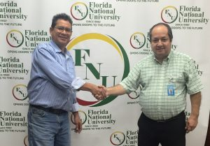 Dental director Dr. Restrepo poses with Alumnus in front of FNU Banner