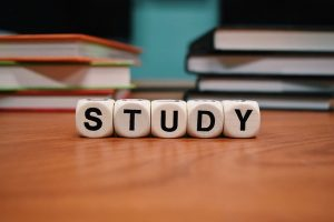 """books on a desk with lettered dice spelling """"study"""" in front"""