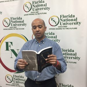 FNU Grad and Author Anibal poses while holding his book