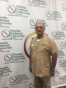 Ricardo Sanchez in front of FNU logo