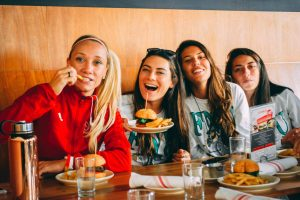 Women's Soccer poses for a photo at a restaurant