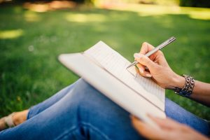 FNU April Poetry Month. Person poses with notebook and pen on grass.