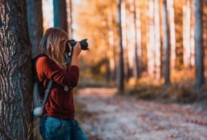 woman taking photos with camera in woods