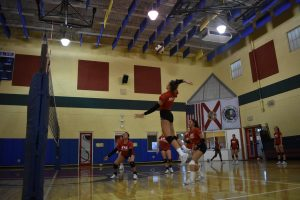 fnu volleyball player attacking the ball in the air