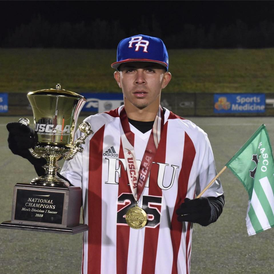 George Perez FNU Soccer Player holding a National Champions trophy