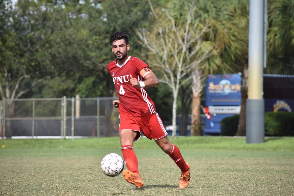 FNU Men's soccer player dribbling the ball