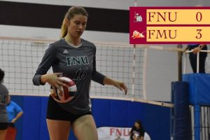 FNU Volleyball player holding the ball. in the up left corner the game score FNU 0 FMU 3