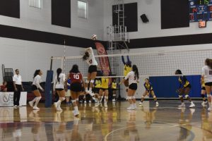FNU Volleyball player attacking the ball and opponent players trying to block the ball