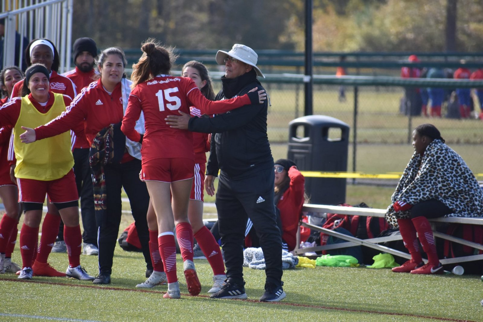 Women's soccer player Mickaela celebrating a goal with coach Giovanni