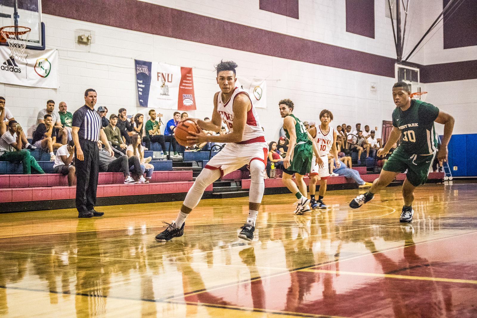 Men's basketball player Nico Rojas holding the ball