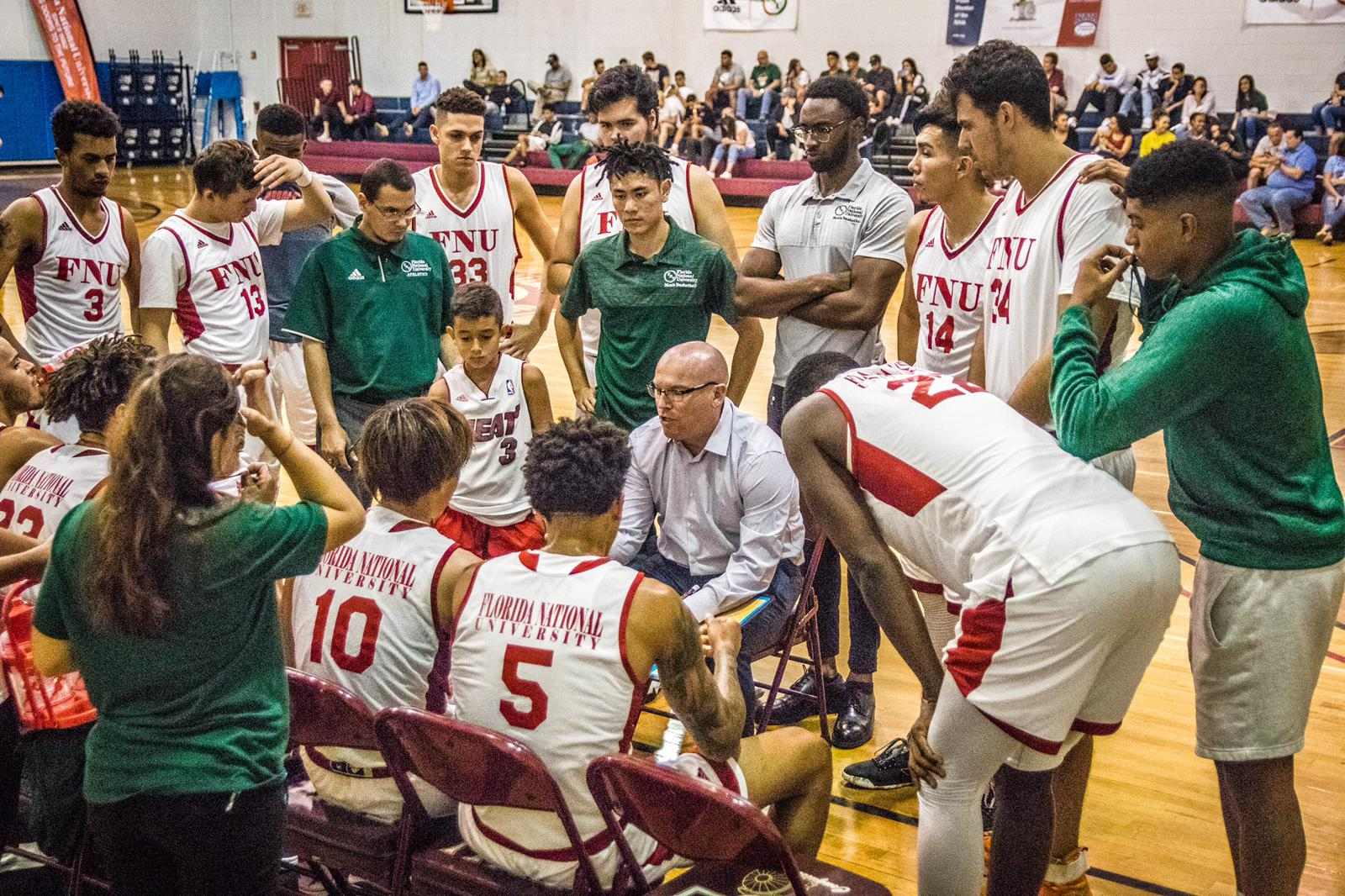 fnu men's basketball team listening to coach JJ during a time-out