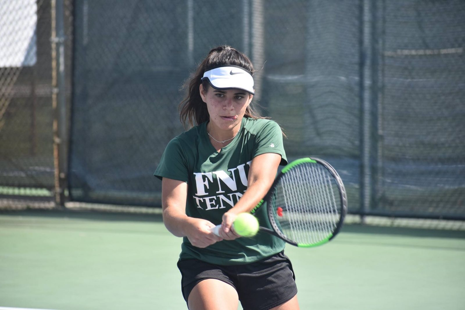 FNU tennis player Candela hitting the ball