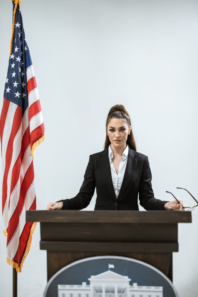 Lady standing at podium with American Flag. What is Public Administration?